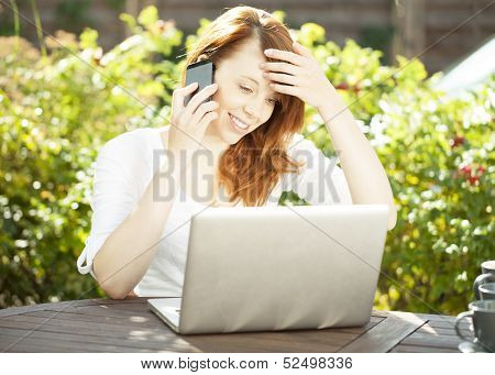 Smiling Woman Sitting In The Garden Using A Mobile