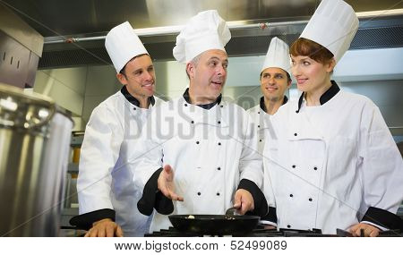 Experienced head chef explaining food to his colleagues in the kitchen