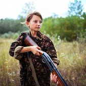stock photo of shotgun  - Young beautiful girl with a shotgun in an outdoor - JPG