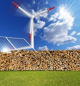 stock photo of turbines  - Solar panels firewood logs in a pile and a turbine power station  - JPG
