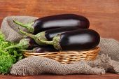 stock photo of wooden basket  - Fresh eggplants in wicker basket on table on wooden background - JPG