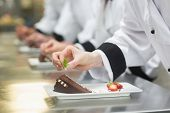 image of dessert plate  - Team of chefs in a row garnishing dessert plates in a busy kitchen - JPG