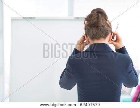 Stressed Business Woman Near Flipchart. Rear View