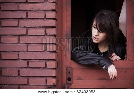 Young beautiful woman portrait on rusty window