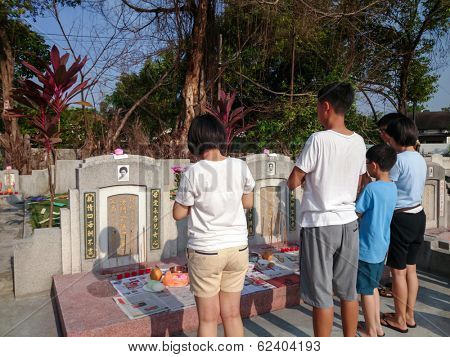 PETALING JAYA MARCH 30: Family members pray at their ancestors graves on Tomb Sweeping Day or the Qingming festival on March 30, 2014 in Petaling Jaya, Malaysia. This tradition dates back 2,500 years.