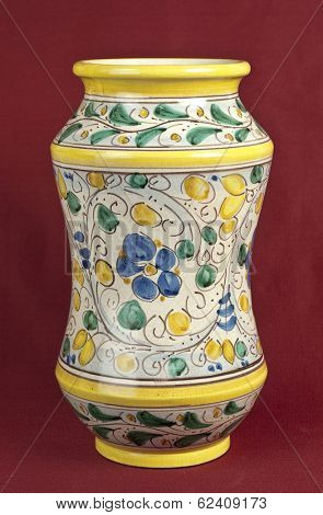 Old decorated pharmacy jar on oxblood red background
