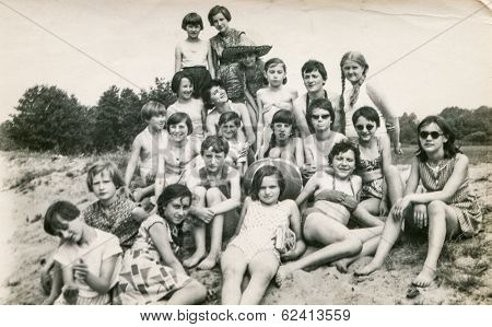 POLAND, CIRCA 1970's: Vintage photo of group of  young girls and teachers posing together  during a summer camp