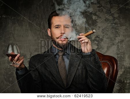 Handsome well-dressed with glass of beverage and cigar