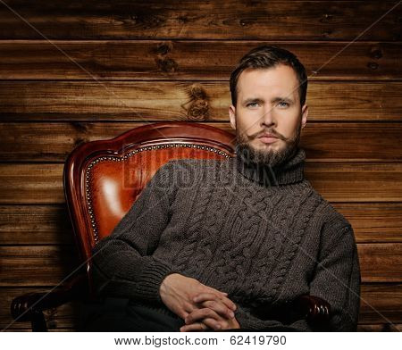 Handsome man wearing cardigan in wooden rural house interior