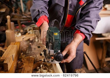 Carpenter At Work With Electric Planer Joinery