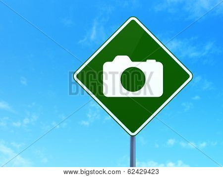 Vacation concept: Photo Camera on road sign background