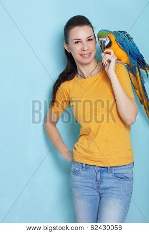 Portrait of a young woman with her domestic ara parrot