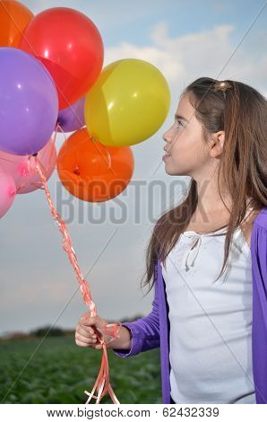 A Teenage Girl In Purple With Colorful Balloons