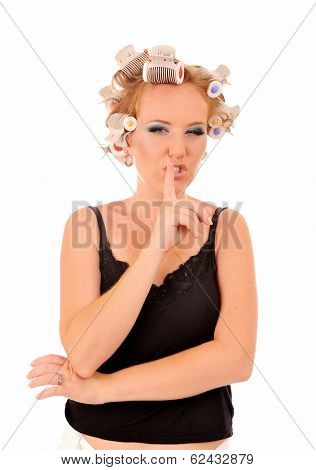 Funny woman with curlers saying shhh, be quiet.