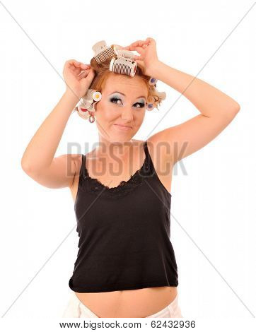 Funny young woman makes hair curlers.