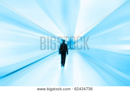 Toned image of blurred man walking in subway station.