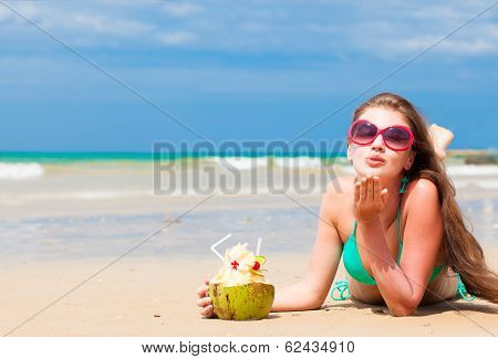 portrait of fit young woman in bikini with coconut on the beach blowing air kiss