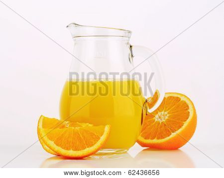 glass pitcher of orange juice with fresh oranges
