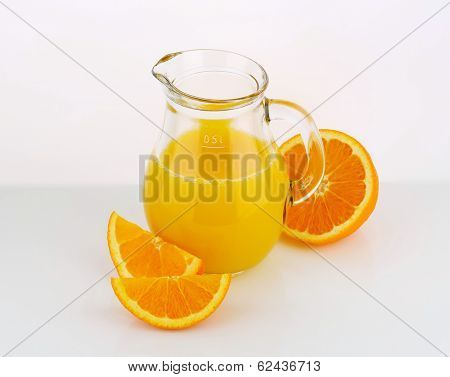 freshly squeezed orange juice n the glass pitcher, decorated with pieces of fresh oranges