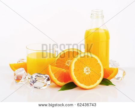 orange juice in the glass and bottle, decorated with fresh oranges and ice cubes
