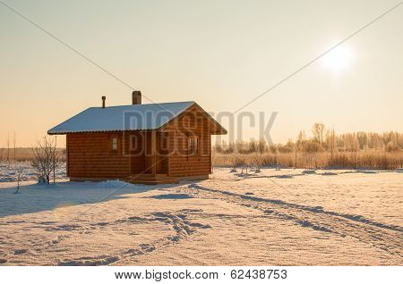 wooden saun house in snow and frozen landscape