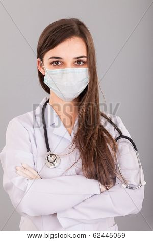 Doctor / Nurse Smiling Behind Surgeon Mask. Closeup Portrait Of Young  Caucasian Woman Model In Whit