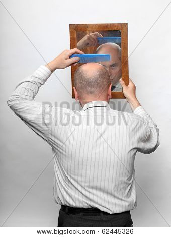 Funny picture of a hairless man combing his hairdo against mirror.