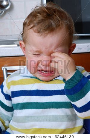 Crying baby in the kitchen.Crying child.Little child crying.