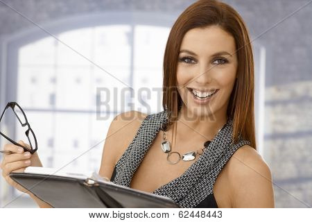 Closeup portrait of beautiful young businesswoman with personal organizer.