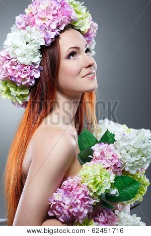 Close-up portrait of beautiful young redheaded girl in a chaplet with  flowers