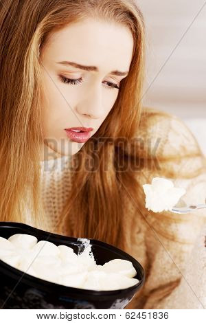 Young depressed woman is eating big bowl of ice creams to comfort herself. Depression, bulimia and diet concept.