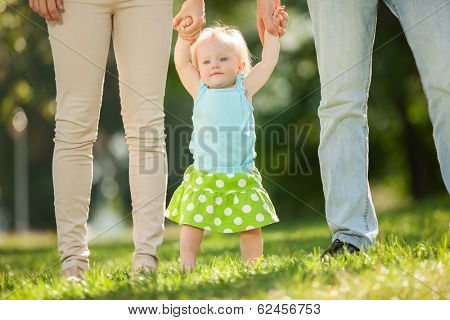 Mother, father and daughter in the park. First steps