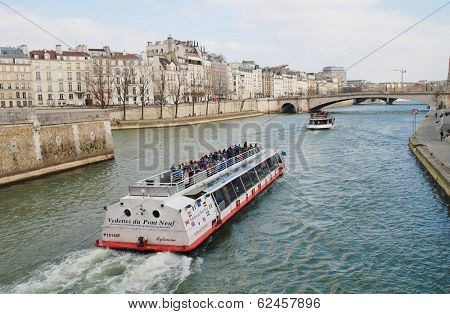 PARIS, FRANCE - MARCH 18, 2014: Excursion boats head towards the Pont De La Tournelle on the River Seine. Numerous such boats ply the Seine each day, passing many famous Paris landmarks.