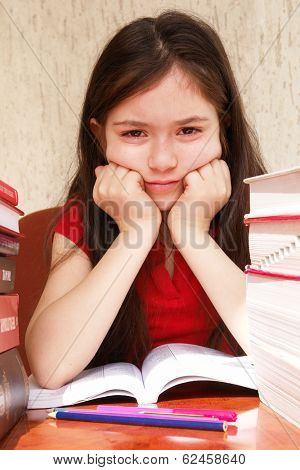 Tired school girl with piled books on homework desk