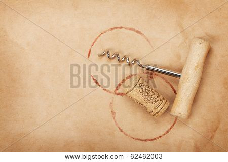 Corkscrew and cork with red wine stains on brown paper background with copy space