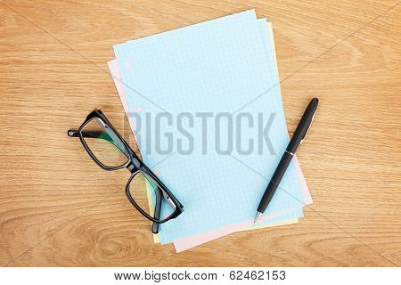 Blank lined paper with office supplies and glasses on wooden table. Above view