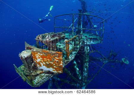 Free diver exploring the ship wreck in tropical sea