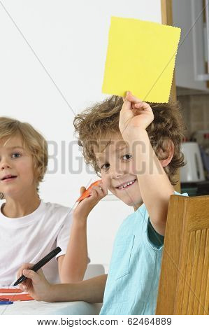young boy holds up a blank piece of yellow paper