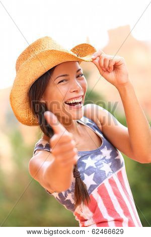 American cowgirl woman happy excited giving thumbs up wearing cowboy hat outdoors in countryside. Cheerful elated joyful woman smiling enjoying freedom. Beautiful multiracial Asian Caucasian female.