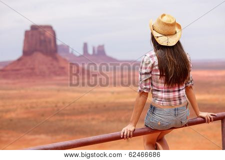 Cowgirl woman enjoying view of Monument Valley wearing cowboy hat. Beautiful young woman on sitting looking outdoors, Arizona Utah, USA.