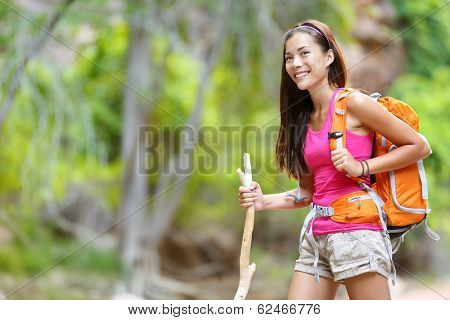 Asian woman hiker hiking in forest standing with backpack and wooden hike stick smiling happy living healthy active outdoor lifestyle. Beautiful young mixed race Asian Caucasian female model.