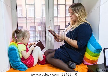 Pretty Girl With Young Mother Read Books On The Window Sill