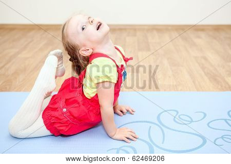 Flexible Child Making Gymnastics On Floor
