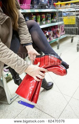 Customer Trying Red Rubber Boots In The Shop