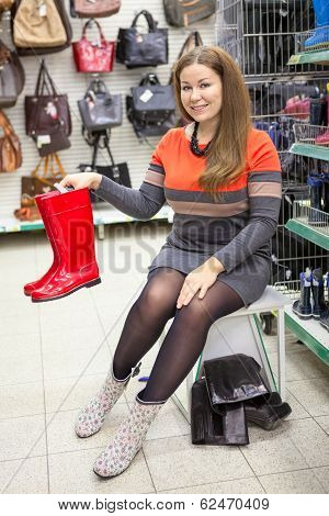 Smiling Customer Showing Red Rainboots When Dressing Shoes