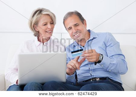 Happy Mature Couple Shopping On Laptop