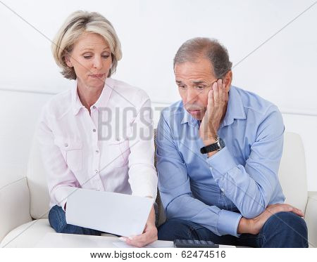 Shocked Couple Looking At Bill