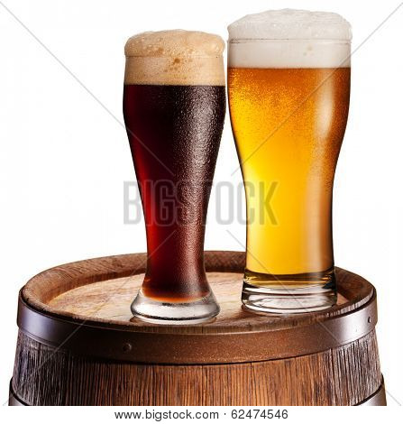 The glasses of beer over woden barrel. File contains clipping paths.