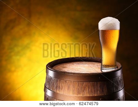 The glass of beer over woden barrel on the golden background.
