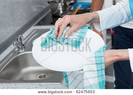 Close-up Of Woman Cleaning Utensils